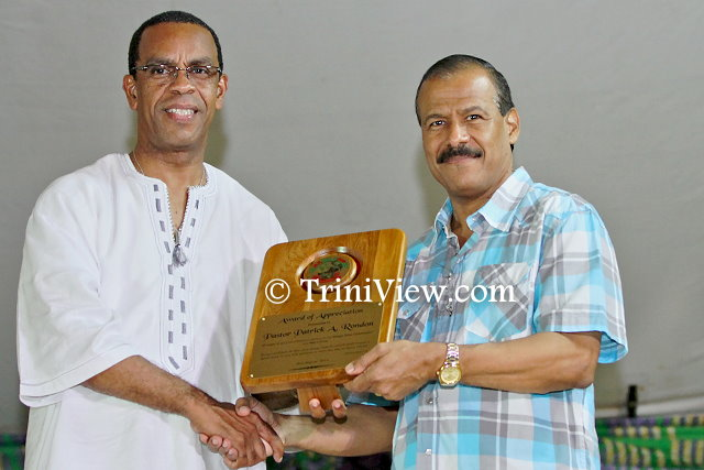 (L) Minister, the Honourable Rodger Samuel, presents a token of appreciation to Pastor Rondan