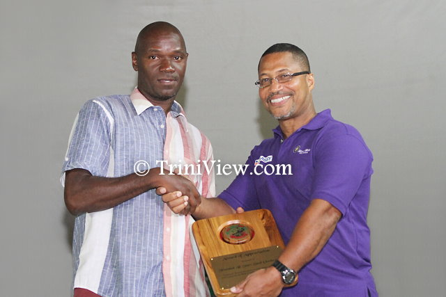 (R) Member of Palo's Crew presents a token of appreciation to a member of Neal & Massy Trinidad All Stars Steel Orchestra